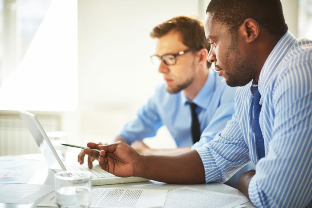 パソコン画面を示して同僚と話す男性