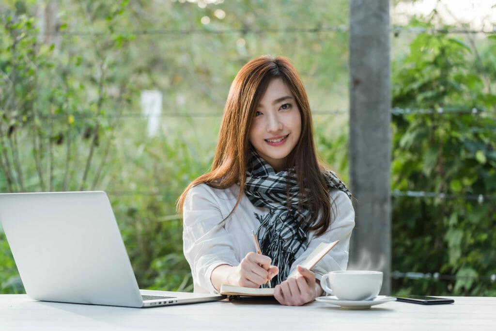 美しい10代の女性はラップトップPCでフリーランスとして働く