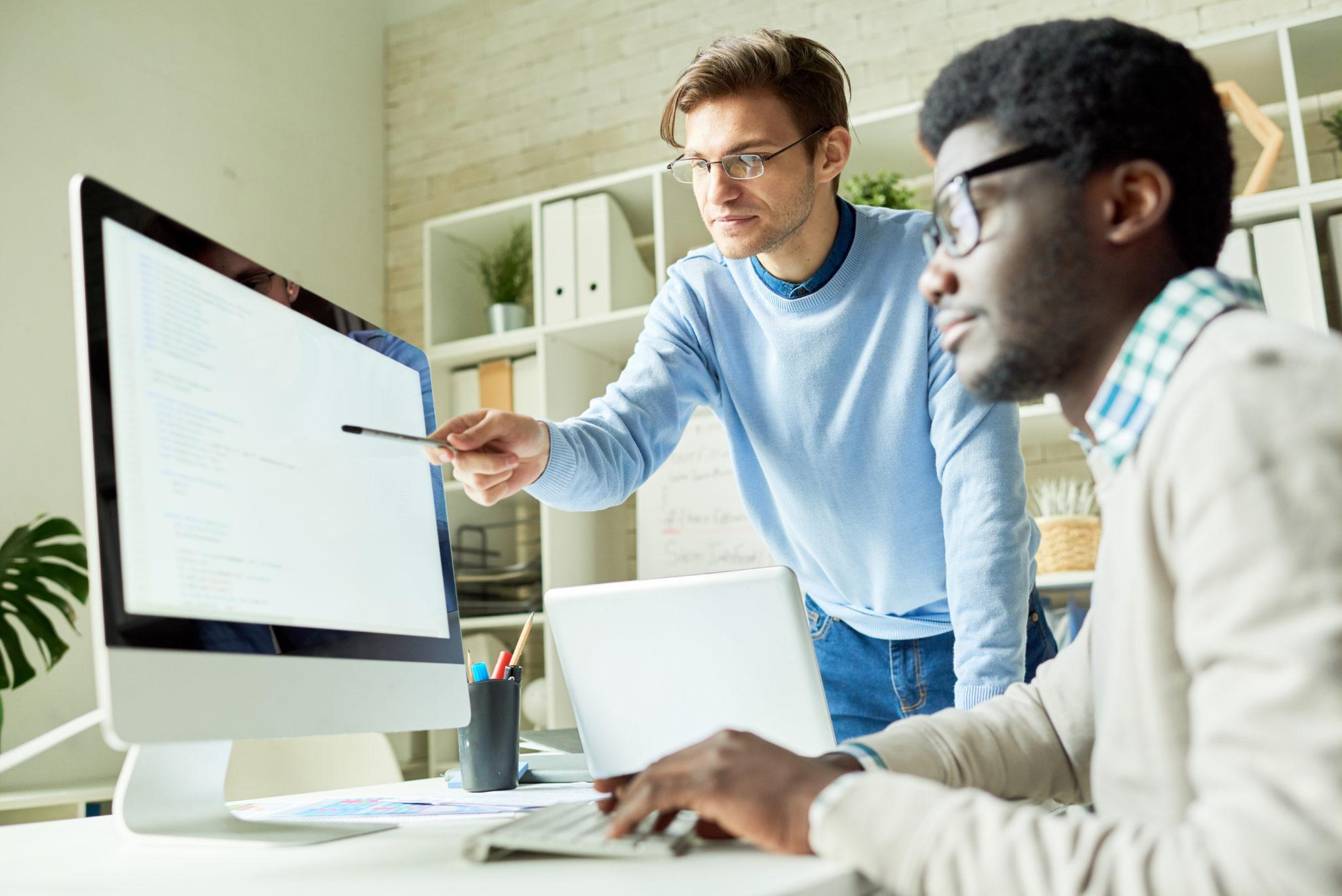 パソコンの画面を見る男性たち
