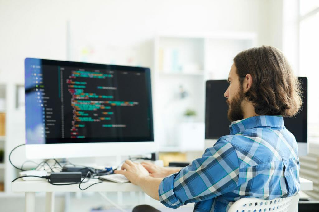 デスクトップでコーディングする若い男性