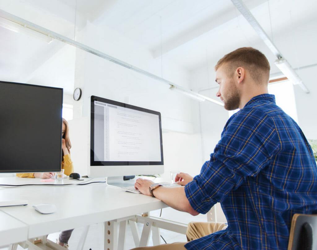オフィスのパソコンの前にいるクリエイティブな男性