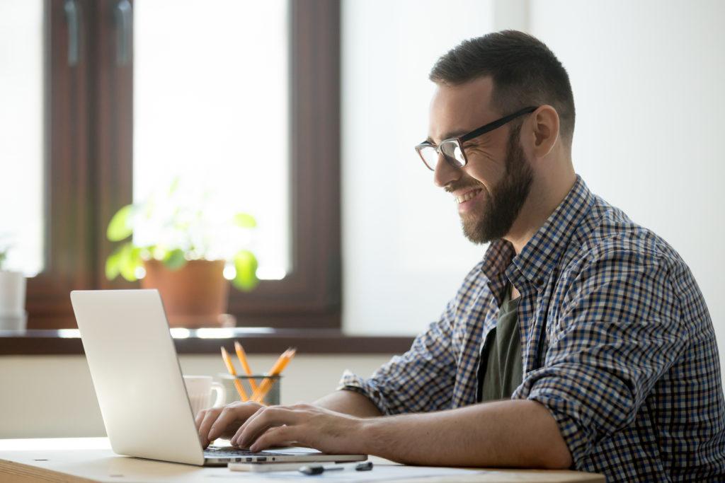 嬉しそうにパソコンを触る男性