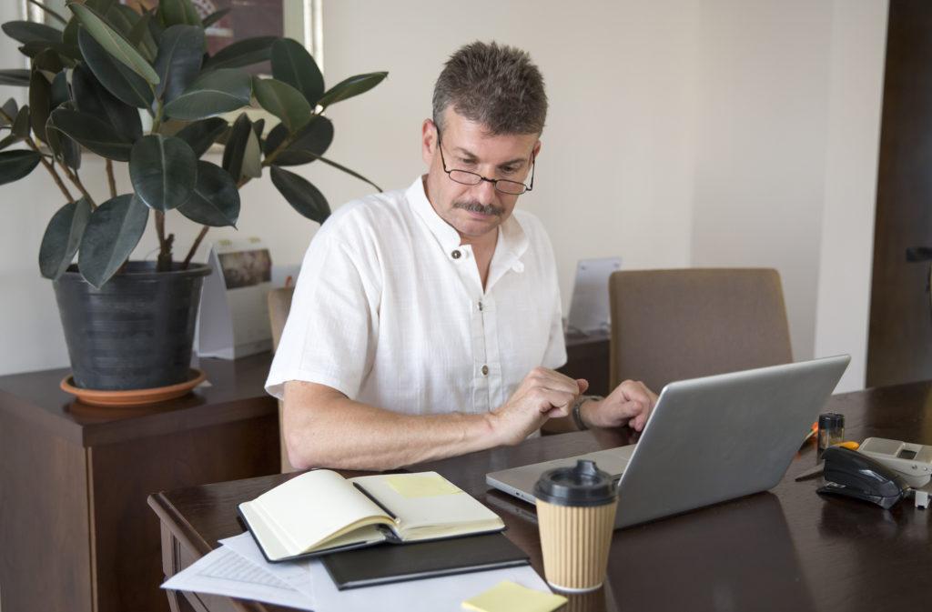 家のオフィスでパソコンを使って働く中年男性