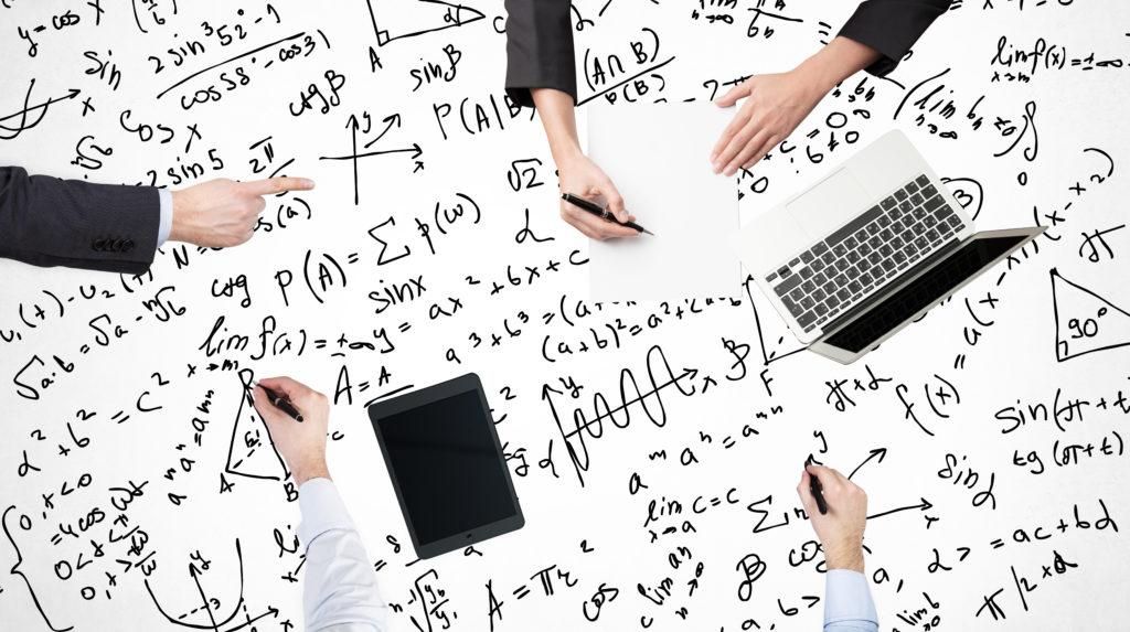 ブレーンストーミングプロセスの平面図。同僚は数学の問題を解決しています。テーブルの表面にラップトップ、タブレット、数学の数式が描かれています。