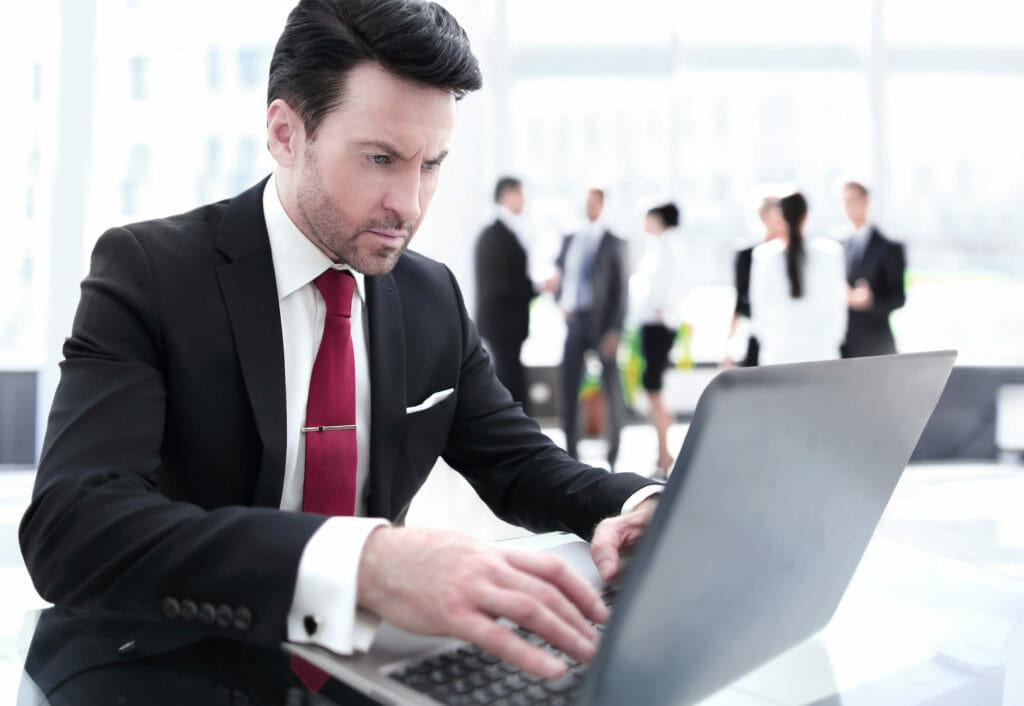 ラップトップコンピュータでタイピングするビジネスマン