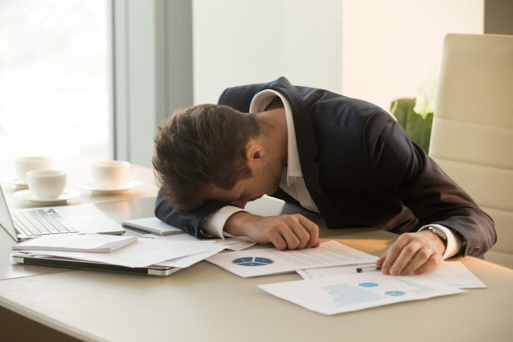 オフィスのデスクで疲れ果てている若い男性