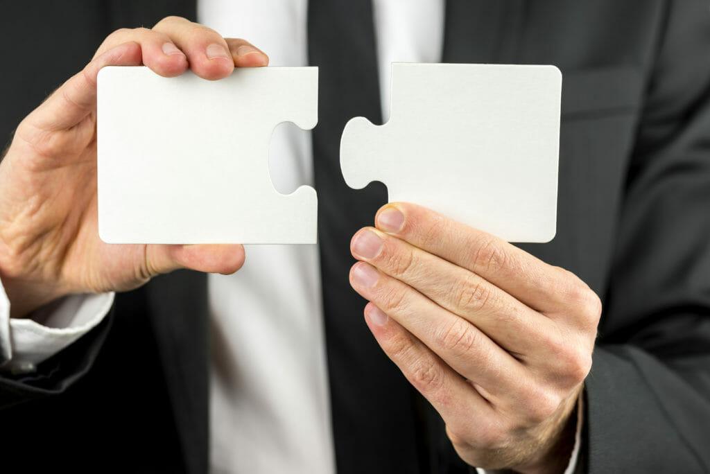 空白のパズルの2つの部分を保持している実業家