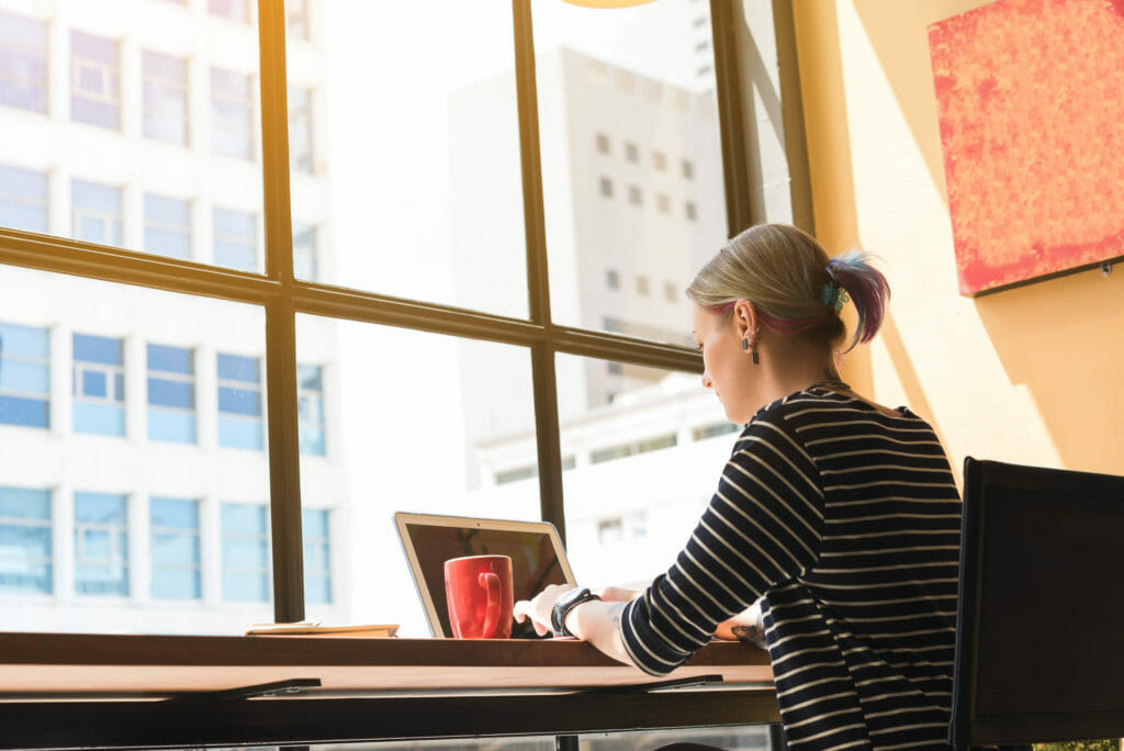 喫茶店にてラップトップPCでフリーランスの仕事をする