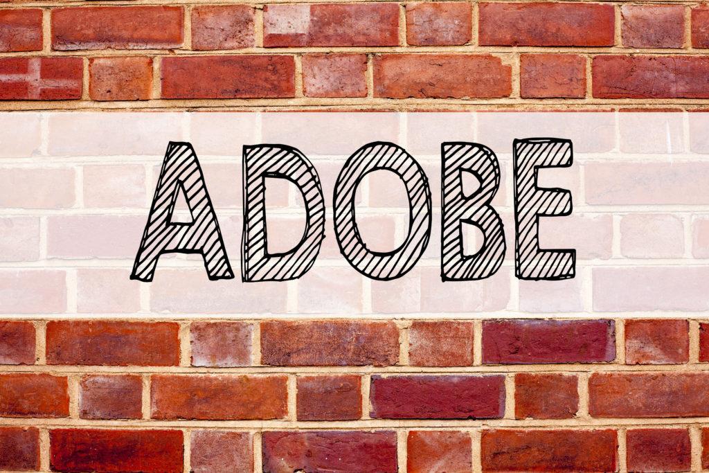 概念の発表テキスト キャプションのインスピレーション ADOBE を示します。スペースに古いレンガの背景に書かれたソフトウェア会社名のビジネス コンセプト