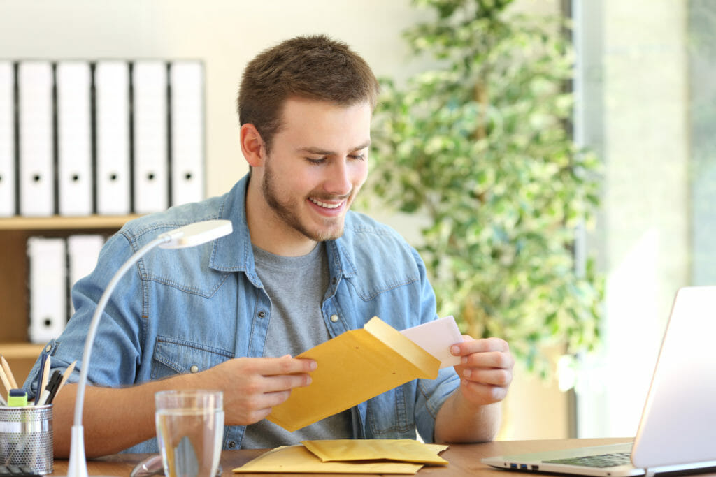 起業家のオフィスでデスクトップで詰め物をした封筒を開く