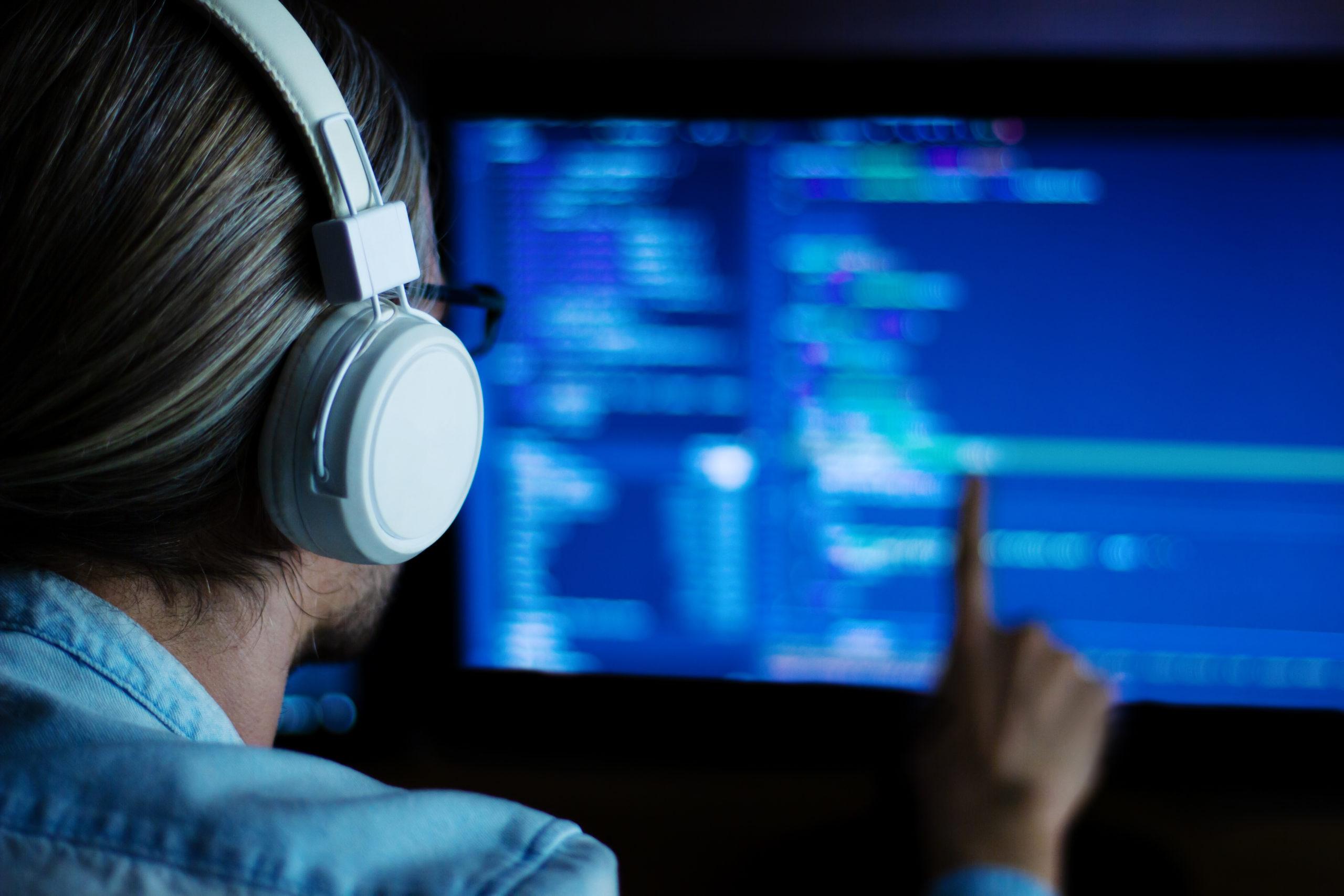 白いヘッドフォンとプログラムコードで動作する眼鏡を備えたソフトウェア開発者フリーランサー:C ++、Java