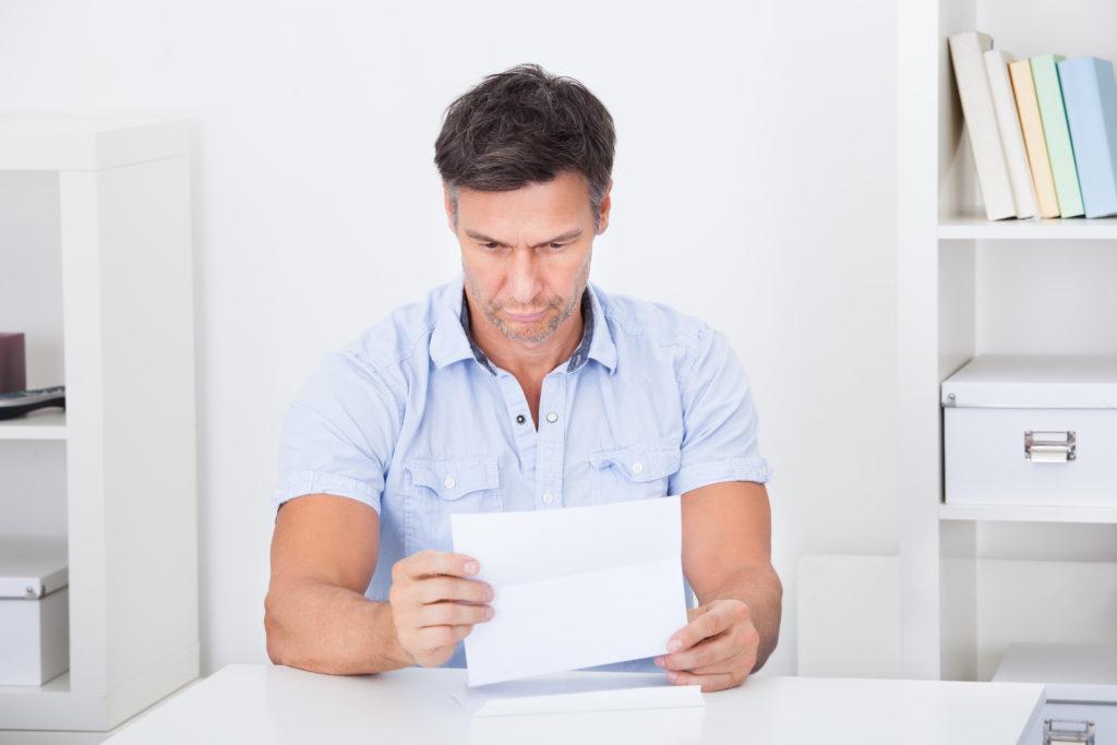 紙を見る男性