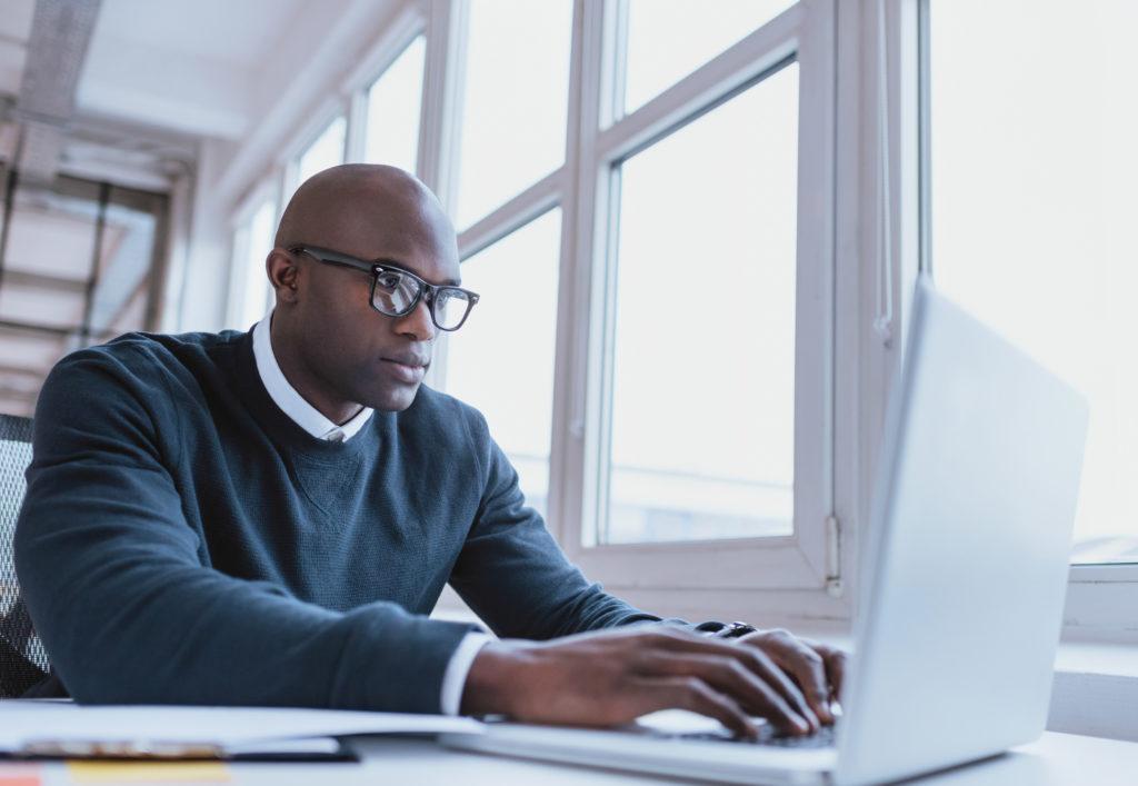ラップトップパソコンで仕事をしているアフリカ系アメリカ人男性