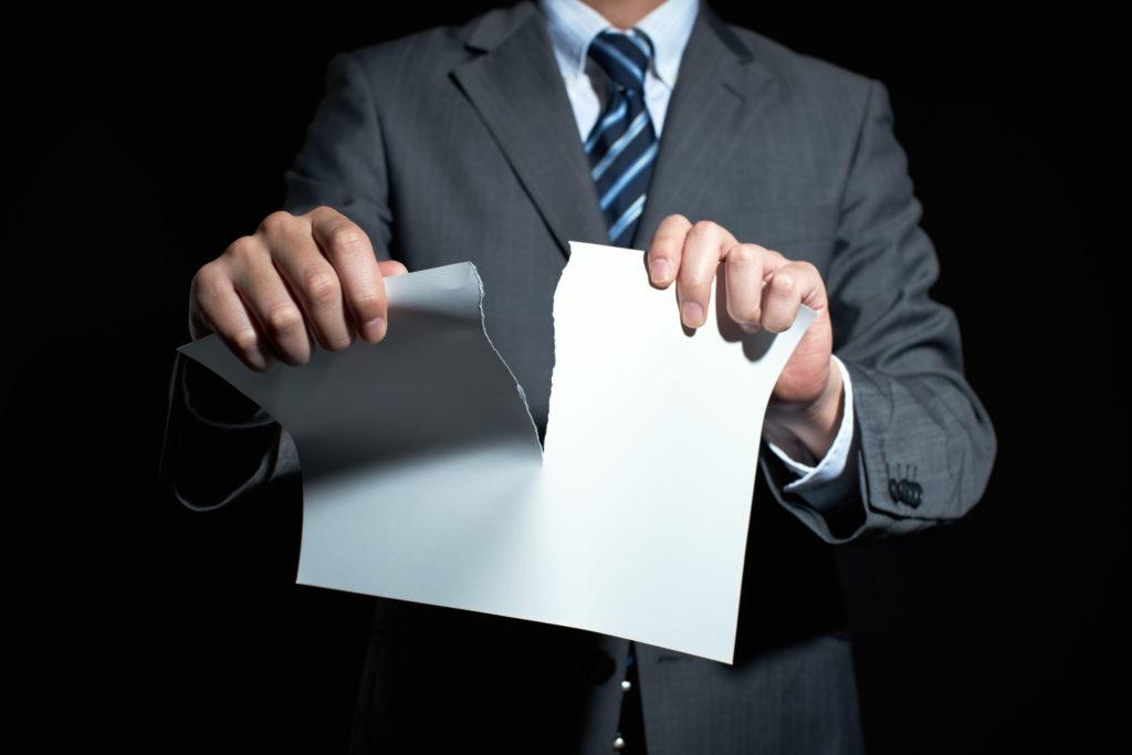 紙を破る男性