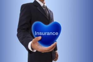 ビジネスマンが「保険」の字を記したハートを手に持っている