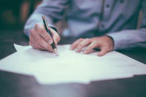 紙にペンで描く男性